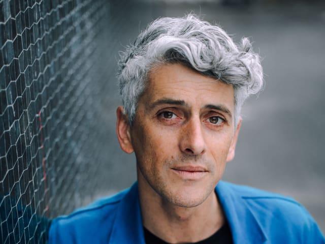 Mann mit grauer Tolle, blauer leichter Jakce steht an einer Wand und schaut in die Kamera.