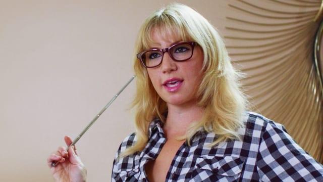 Eine blonde Frau mit Brille und kariertem Hemd.