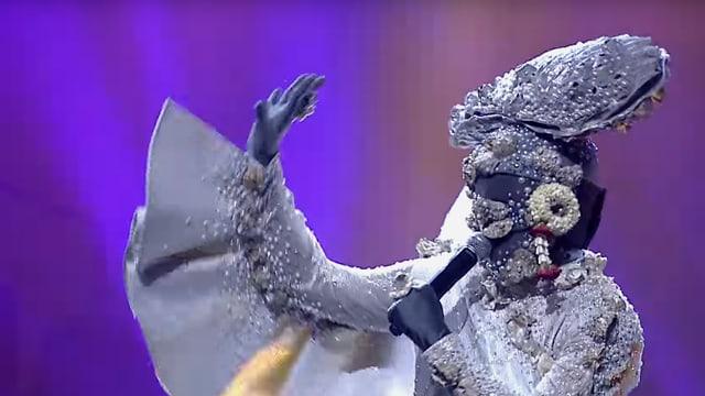 Ein Mann im Austern-Kostüm hält ein Mikrofon in der Hand.
