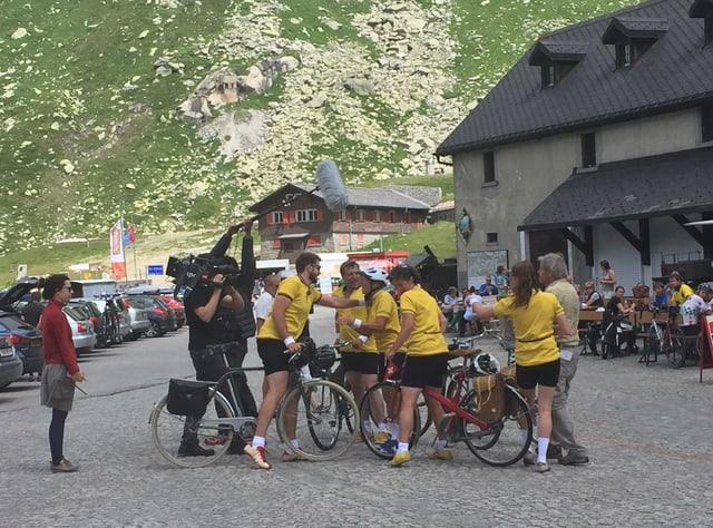 Velofahrer in gelbem Trikot stehen mit ihren Rädern auf dem Gotthardpass zusammen.