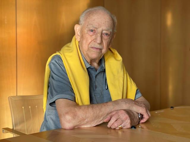 Mann mit gelbem Pullover sitzt am Tisch