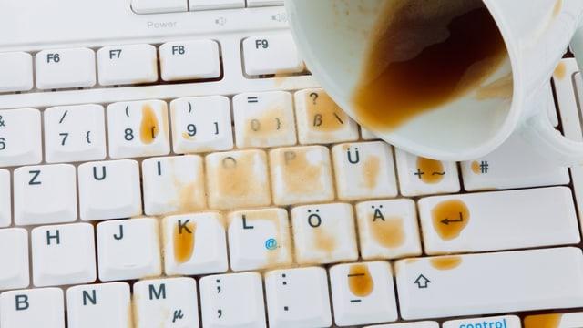 Eine umgeworfene Kaffeetasse auf einer Tastatur