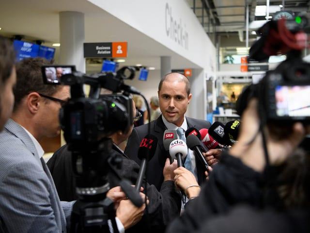 Mann, umringt von zahlreichen Medienleuten
