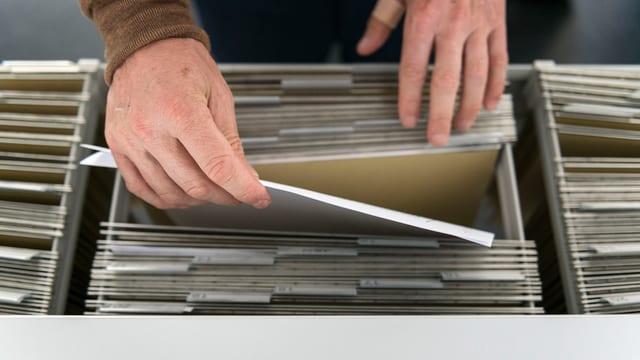 Hand nimmt Akte aus Schublade