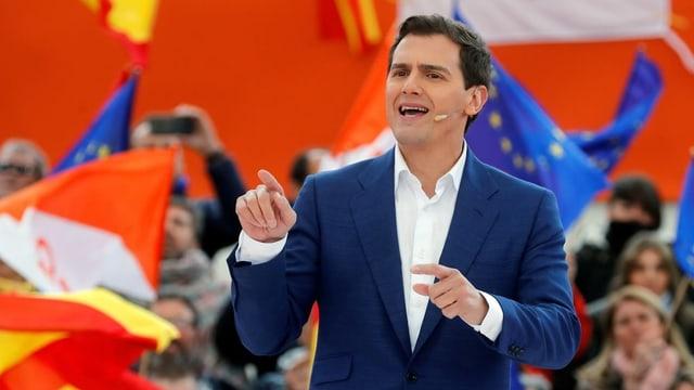 Albert Rivera spricht in einem blauen Blazer an einer Wahlkampfveranstaltung. Hinter ihm rote und EU-Fahnen.