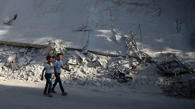 Zwei Knaben laufen durch eine Strasse voller Schutt in Damaskus.