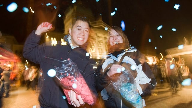 Jugendliche spielen mit Konfetti vor dem Bundeshaus.