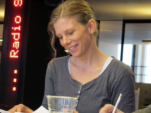 Kerstin Birkeland Ackermann schaut auf ein Papier auf dem Tisch.
