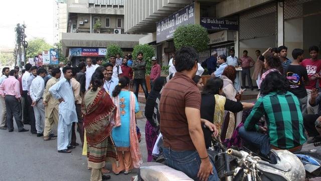 Bewohner der Hauptstadt Karachi stehen auf der Strasse.