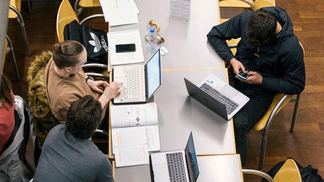 Studenten am Schreibtisch vor dem Laptop und dem Handy.