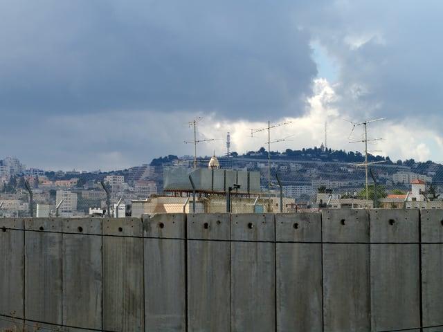 Im Vordergrund eine undurchsichtige Mauer aus grauem Beton, dahinter ein grösseres Dorf.