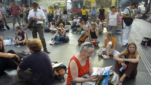 Wartende Menschen sitzen auf dem Boden