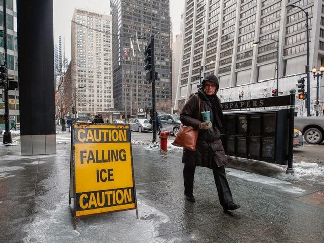 Frau lauft warm eingepackt auf der Strasse.