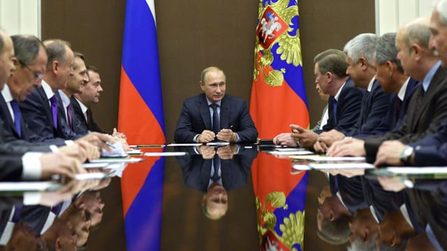 Der russische Präsident sitzt am Kopfende eines Tisches, umgeben von seinen Sicherheitsberatern