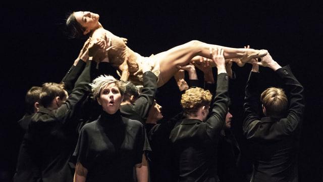 Mehrere Tänzer halten Tänzerin in die Höhe, vorne steht Sängerin.