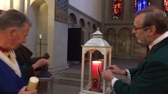 Mehrere Männer stehen um Kerze