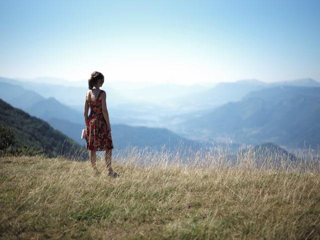Eine Frau steht auf einer Wiese und blickt auf eine wunderschöne Landschaft hinab.
