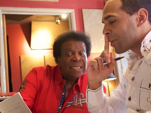 Zwei farbige Männer grübeln über Liedtext.