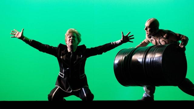 Ein Mann in einer Art Uniform steckt kniend die Arme gegen den Himmel, ein Mann mit nacktem, bemaltem Oberkörper und glattrasiertem Kopf bringt ein schwarzes Fass herbei.