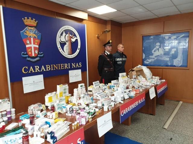 Zwei Polizisten stehen vor einem Tisch mit beschlagnahmten Präparaten.