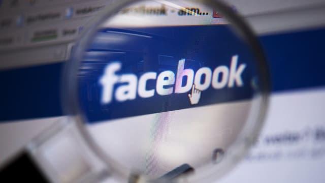 Das Facebook-Logo durch eine Lupe betrachtet.