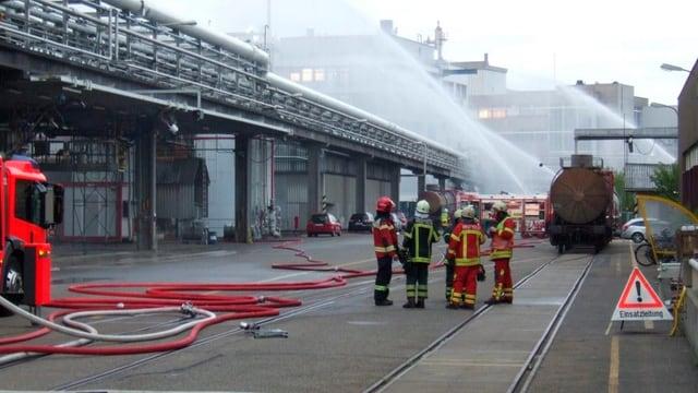 Feuerwehrleute bekämpfen Gaswolke mit Wasser.