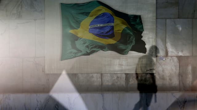 Purtret d'ina bandiera brasiliana reflectada en ina fanestra.