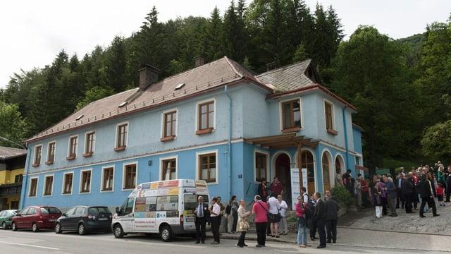 Ein blaues Haus an einer Strasse, davor geparkte Autos und Menschen, die sich unterhalten.