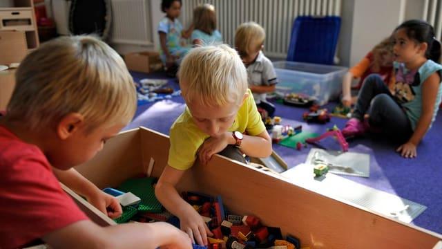 Kindergartensituation: Kinder spielen mit Legosteinen.