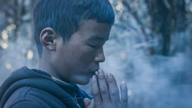 Junge betet am Berg