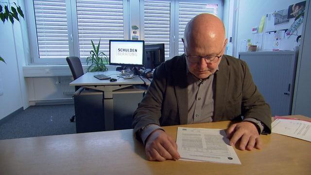 Mann in einem Büro studiert ein Dokument.