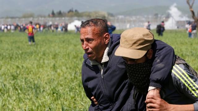 Ein sichtlich angeschlagener, älterer Mann wird von einem jüngeren Flüchtling vom Grenzzaun weggebracht.