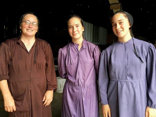 Drei Frauen in Röcken und Hauben.