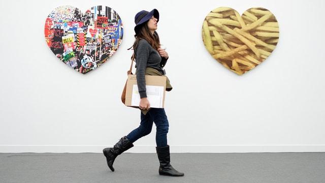 Frau läuft an herzförmigen Bildern vorbei