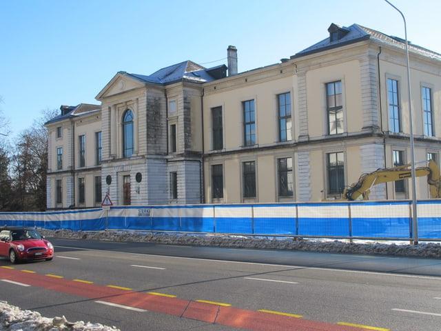Beiges Gebäude mit Baukran und Baugitter davor.