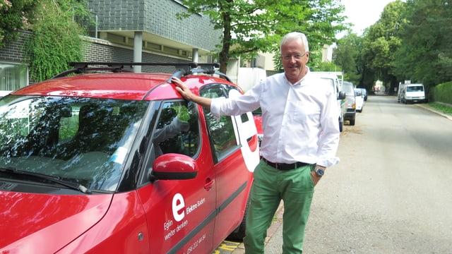 Ein Mann steht bei einem roten Auto.
