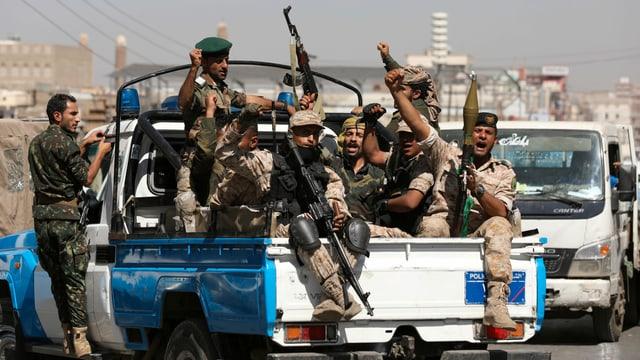Houthi-Rebellen auf der Ladefläche eines Polizei-Autos.
