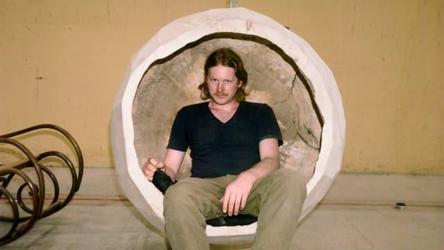 Lukas Wassmann sitzt ein einer Holzkugel.