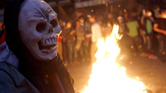 Ägyptischer Demonstrant mit Totenmaske vor einer brennenden Barrikade in Kairo.