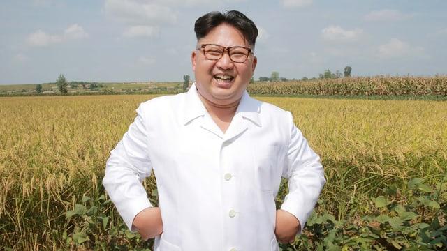 Kim steht vor einem Kornfeld und lacht.