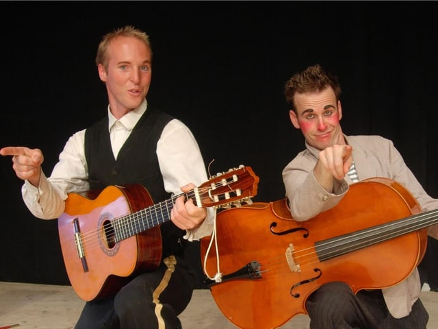 Mann mit Clownnase mit Bass und zweiter Mann mit Gitarre in der Hand auf Bühne.