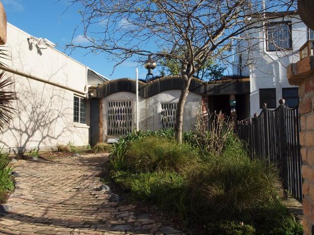 Ein unebener gepflasteter Weg führt zum verspielten Häuschen mit gewölbtem Dach.
