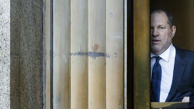 Ein Mann, zur Hälfte verborgen hinter einem Fenster.