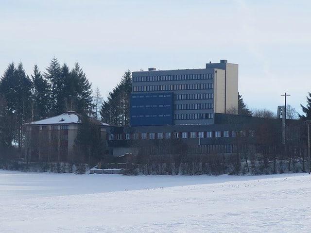 Das Gebäude von weitem - daneben ein weites Feld und Wald.