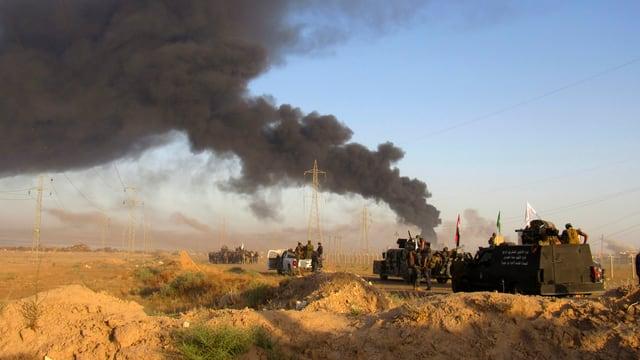 Rauchschwaden über Militärfahrzeugen