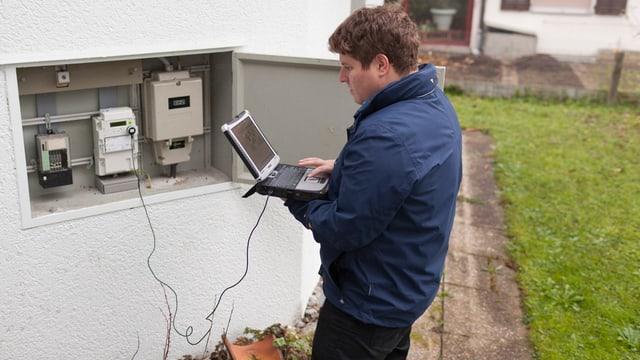 Mitarbeiter der Elektrizitätswerke liest mit Computer Stromdaten ein