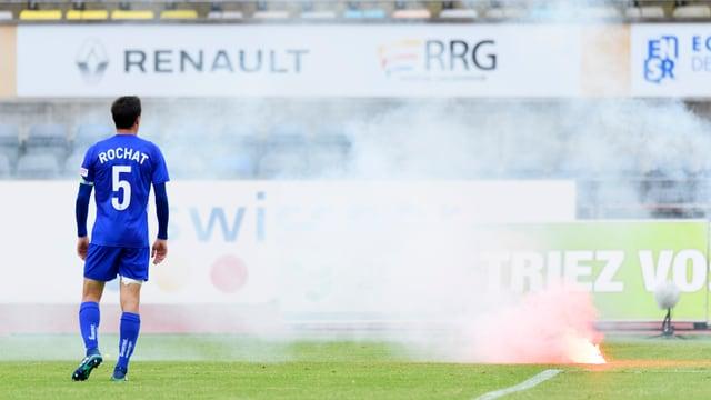 Lausanne-Captain Alain Rochat auf dem Rasen, neben ihm brennt eine Fackel.