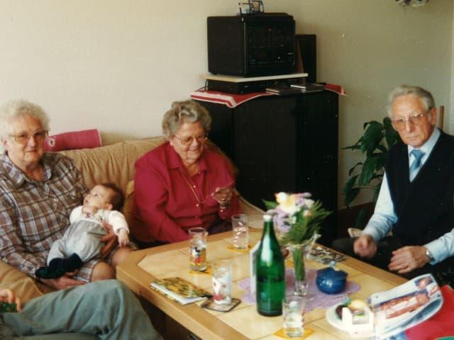 Drei ältere Senioren mit Baby an Wohnzimmertisch.