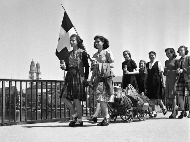 Mädchen ziehen am 8. Mai 1945, dem Tag der Kapitulation Deutschlands, mit einer Schweizer Fahne und einem geschmückten Leiterwagen über die Quaibrücke in Zürich.