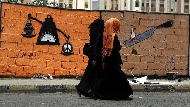 Zwei Frauen gehen an einer Mauer mit einem Graffiti entlang, darauf eine Waage mit einer Bombe und einem Friedenszeichen.